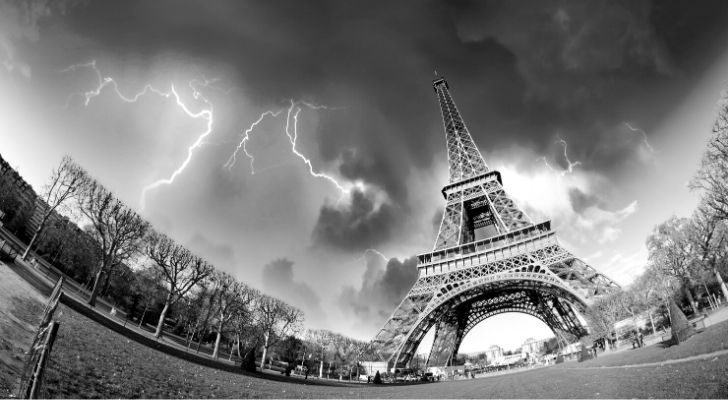 A dramatic photo of the Eiffel Tower with lightning in the sky
