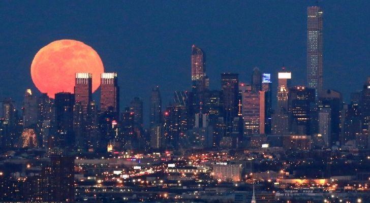 शहर के क्षितिज के ऊपर चमकता हुआ एक गुलाबी सुपरमैन
