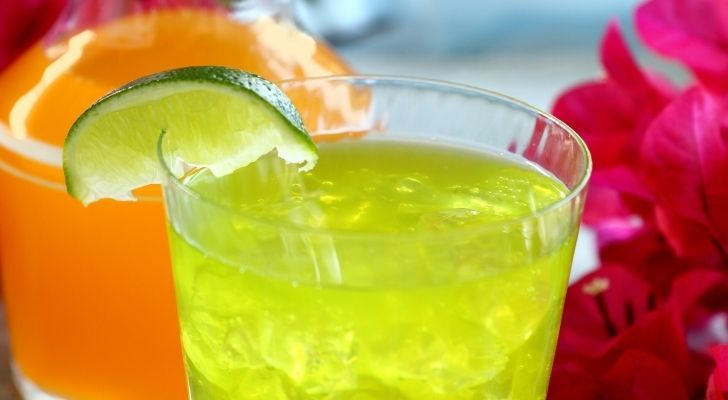A lime drink with a lime wedge on the rim of the glass