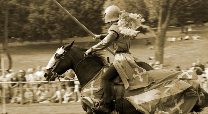 A man riding a horse while jousting