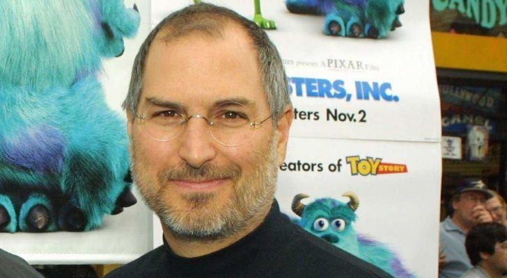 Steve Jobs with a Pixar poster behind him