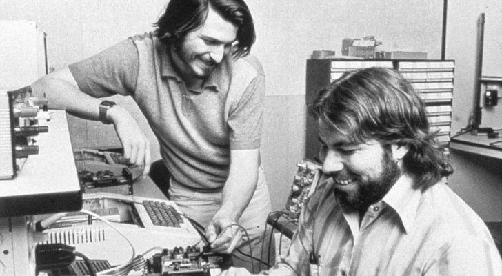 Steve Jobs and Steve Wozniak working on a computer