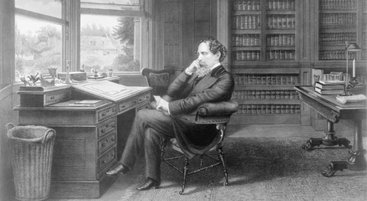 Charles Dickens sitting at an office table
