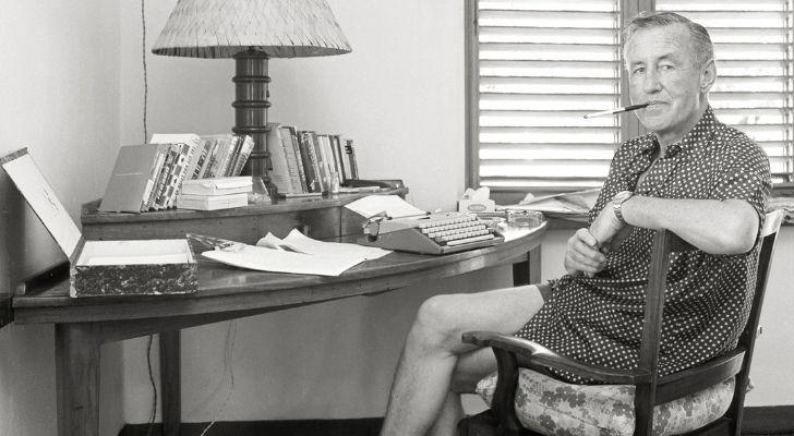 Ian Fleming sitting at his writing desk