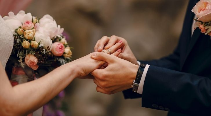 A couple placing rings on each others fingers at their wedding