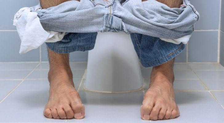 A man sitting on the toilet