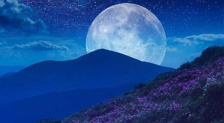 A full June moon behind mountains