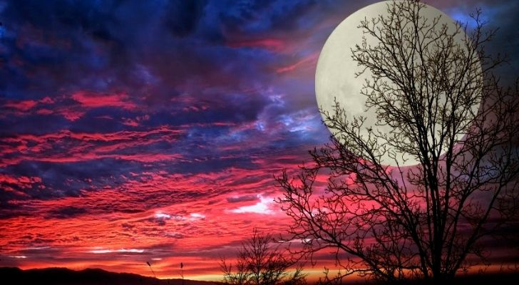 A full moon with a rich pink, red and purple sky