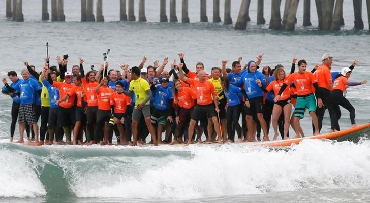 66 people on one big surfboard riding a wave