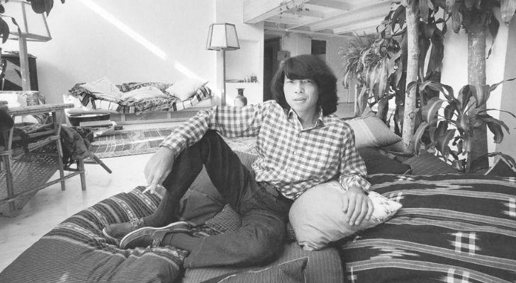 Kenzo Takada black and white photo sitting on a sofa